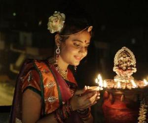 Układanka Kobieta klęczy z lampy naftowej w niej strony w obchodach Diwali
