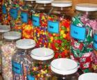 Szklane pojemniki z różnymi rodzajami cukierków
