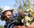 Dziecko z prezentem dla jego matki, duży bukiet kwiatów